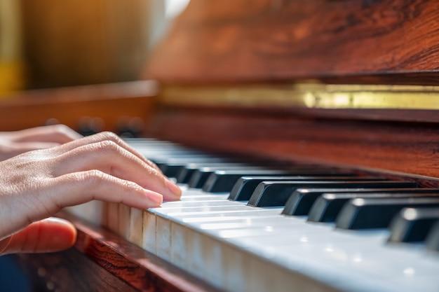 Imagem aproximada de mãos tocando um piano de cauda de madeira vintage