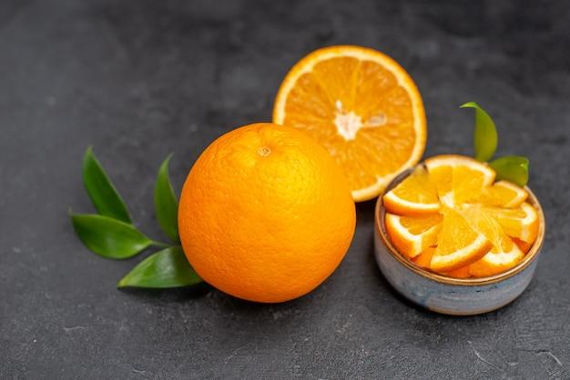 Imagem aproximada de metades de laranja recém-cortadas em limões inteiros na mesa escura