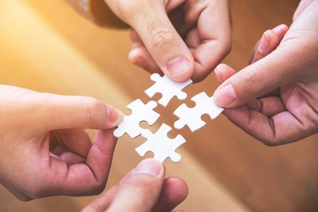 Imagem aproximada de muitas pessoas com as mãos segurando e montando uma peça do quebra-cabeça branco