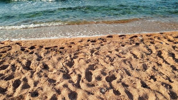 Imagem aproximada de ondas calmas do mar rolando na areia molhada na praia do mar