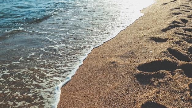 Imagem aproximada de ondas calmas do mar rolando na areia molhada na praia do mar Foto Premium