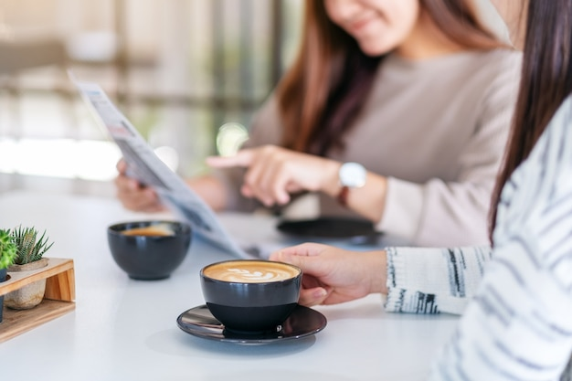 Imagem aproximada de pessoas conversando, lendo jornal e tomando café pela manhã