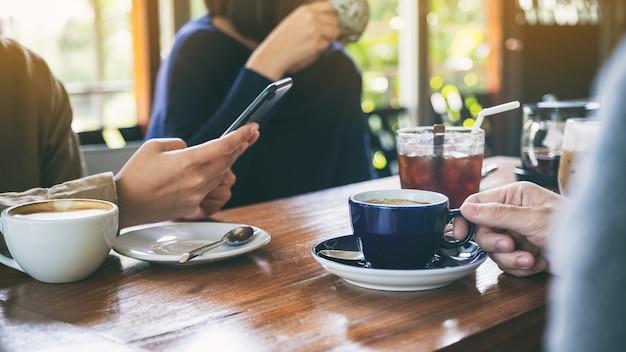 Imagem aproximada de pessoas usando um telefone celular e tomando café juntas em uma cafeteria