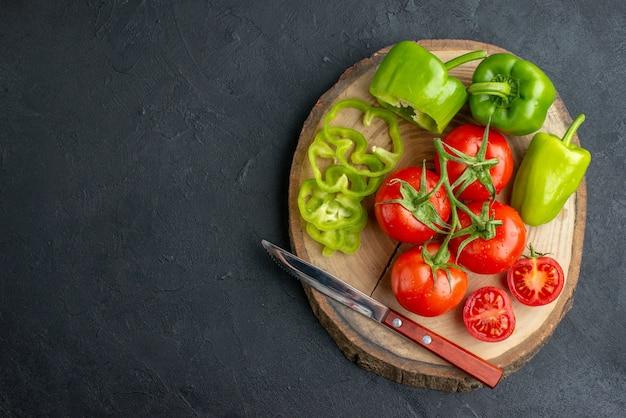 Imagem aproximada de pimentões verdes cortados inteiros e tomates frescos em uma tábua de madeira no lado esquerdo na superfície preta