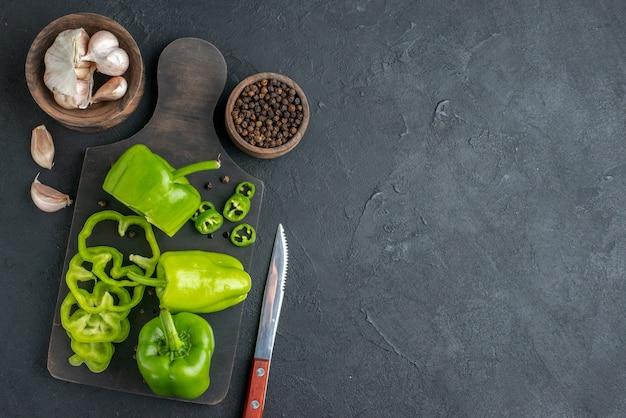 Imagem aproximada de pimentões verdes cortados inteiros em uma tábua de madeira escura no lado direito em uma superfície preta