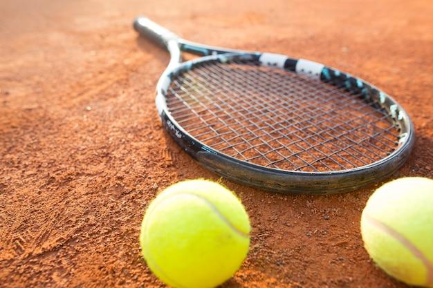 Imagem aproximada de raquete de tênis e bolas na quadra de tênis de saibro, esporte recreativo