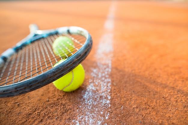 Imagem aproximada de raquete de tênis e bolas na quadra de tênis de saibro