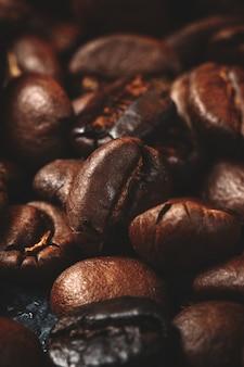 Imagem aproximada de sementes de café marrom no escuro