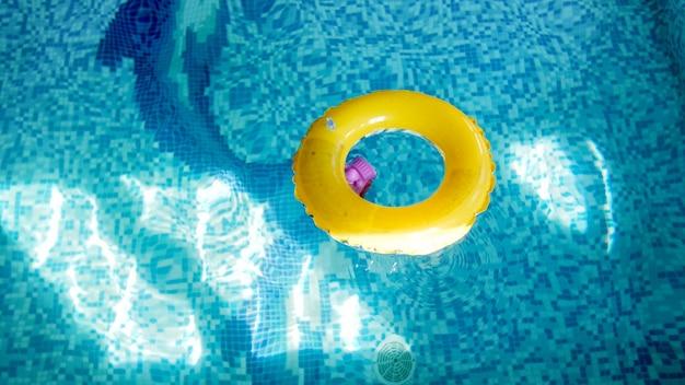 Imagem aproximada de um anel inflável amarelo infantil para nadar na piscina