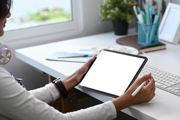 Imagem aproximada de um artista ou designer trabalhando em um tablet digital em um escritório moderno