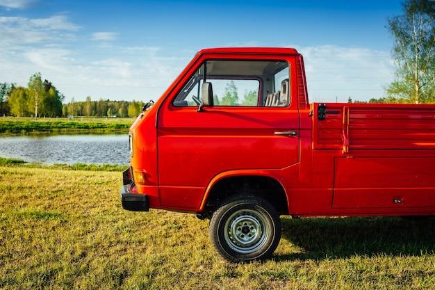 Imagem aproximada de um caminhão vermelho em um campo verde próximo à água