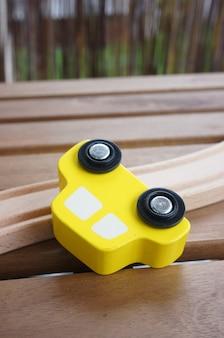 Imagem aproximada de um carro de brinquedo de madeira perto de uma pista de madeira