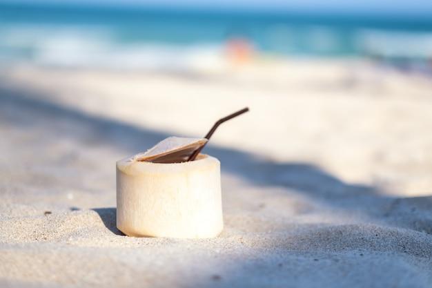 Imagem aproximada de um coco fresco na praia com fundo azul do mar