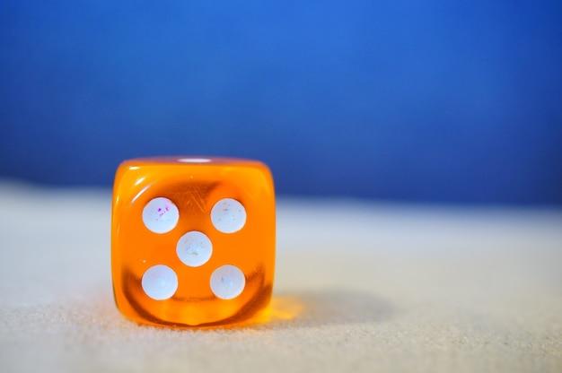 Imagem aproximada de um dado laranja com um fundo desfocado