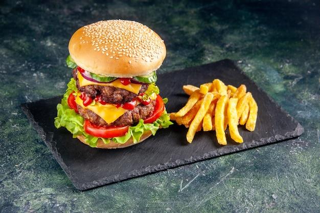 Imagem aproximada de um delicioso sanduíche e batatas fritas na bandeja de cor escura na superfície preta