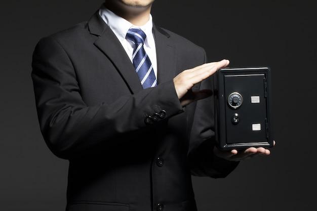 Imagem aproximada de um empresário segurando um pequeno cofre