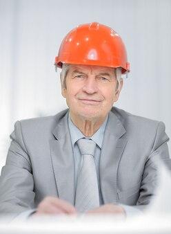 Imagem aproximada de um engenheiro sênior sentado em sua mesa