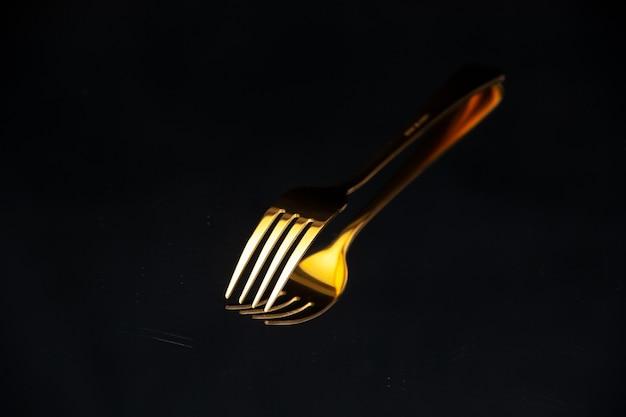 Imagem aproximada de um garfo dourado brilhante colocado de cabeça para baixo sobre um fundo preto desfocado com espaço livre