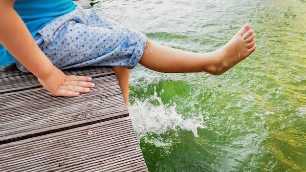 Imagem aproximada de um garotinho descalço sentado na ponte de madeira no lago e espirrando água com os pés