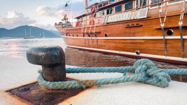 Imagem aproximada de um grande e histórico navio de madeira atracado no porto marítimo