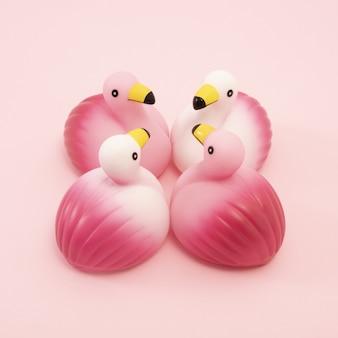 Imagem aproximada de um grupo de flamingos de borracha idênticos, frente a frente