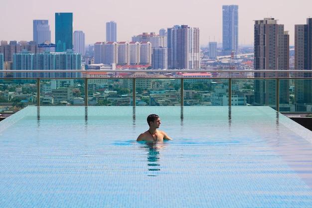 Imagem aproximada de um homem caucasiano nadando na piscina externa localizada na varanda do prédio