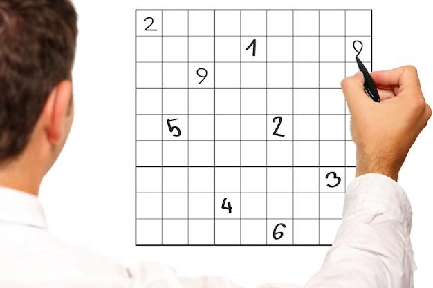 Imagem aproximada de um homem resolvendo sudoku sobre fundo branco