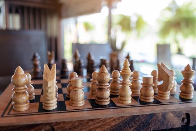 Imagem aproximada de um jogo de xadrez de madeira em um tabuleiro de xadrez