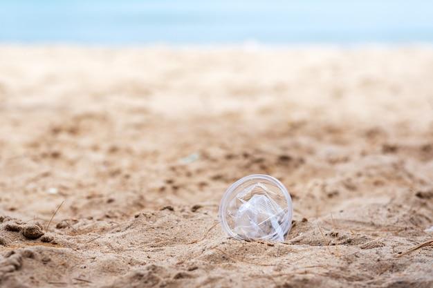 Imagem aproximada de um lixo de vidro plástico na praia