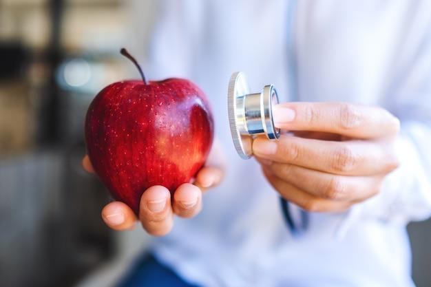 Imagem aproximada de um médico usando um estetoscópio para examinar uma maçã vermelha
