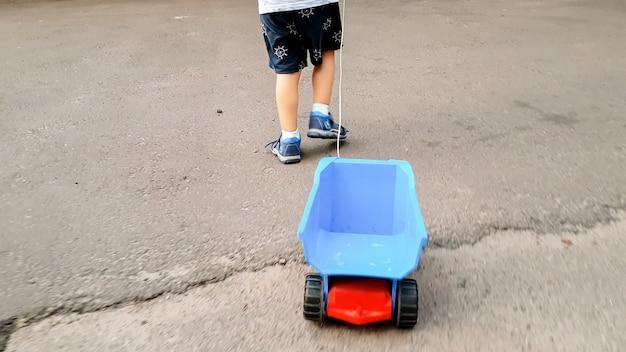 Imagem aproximada de um menino andando na estrada e puxando um grande caminhão de brinquedo por uma corda