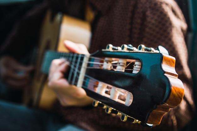 Imagem aproximada de um menino tocando violão dentro do carro