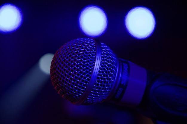 Imagem aproximada de um microfone colocado em um palco durante um evento com luzes ao fundo