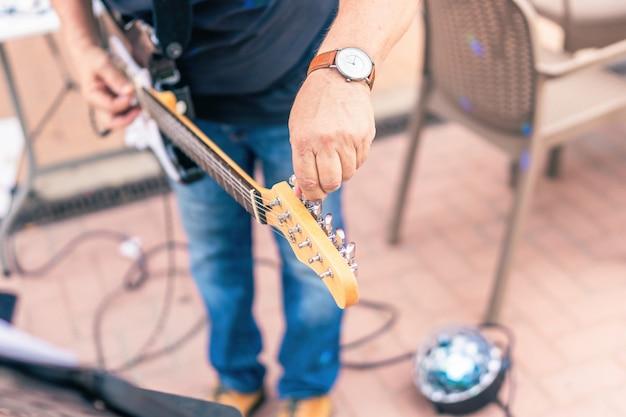 Imagem aproximada de um músico afinando sua guitarra elétrica no palco