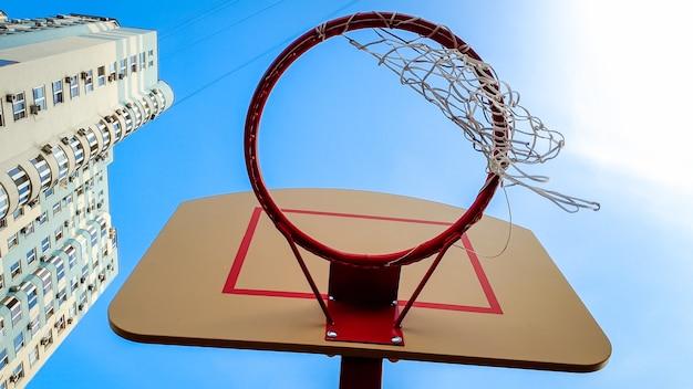 Imagem aproximada de um ringue de basquete com rede contra o céu azul e um prédio alto no distrito residencial da cidade