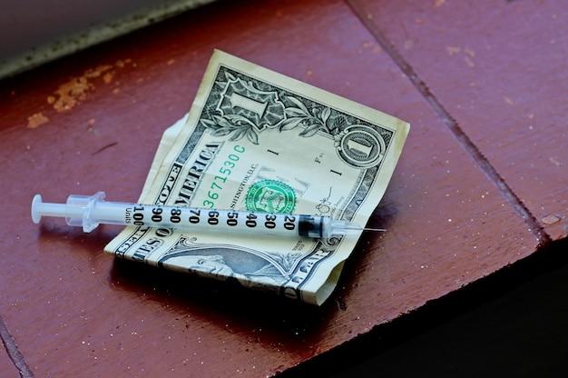 Imagem aproximada de uma agulha em uma nota de um dólar em uma superfície marrom