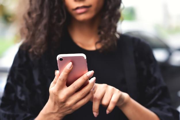 Imagem aproximada de uma bela mulher de raça mista segurando, usando e olhando para seu telefone inteligente