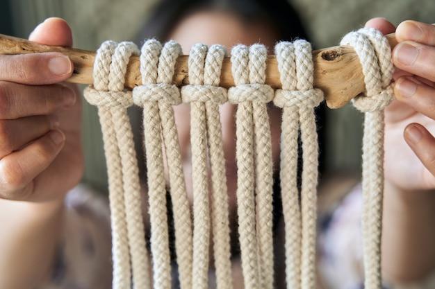 Imagem aproximada de uma decoração de macramê feita à mão por uma jovem