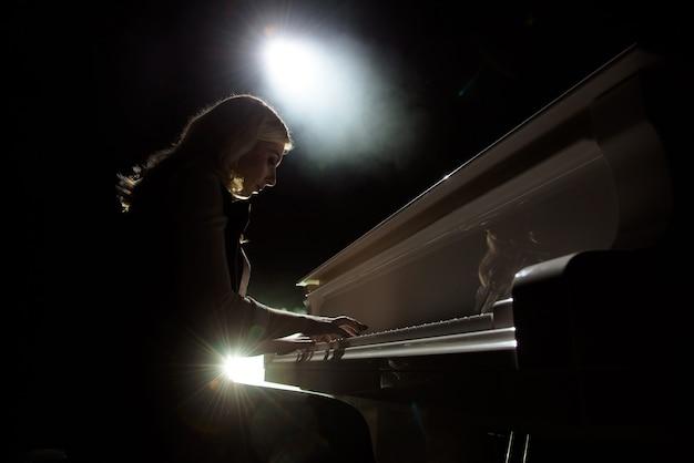 Imagem aproximada de uma garota tocando piano na sala de concertos no local