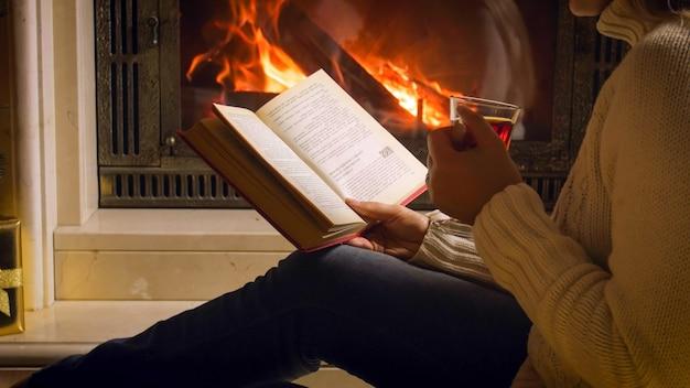 Imagem aproximada de uma jovem sentada junto à lareira com um livro