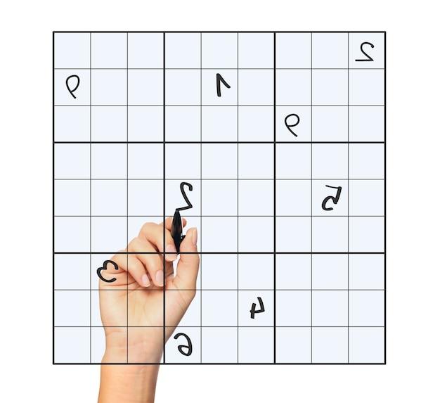 Imagem aproximada de uma mão feminina resolvendo sudoku sobre fundo branco