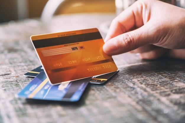 Imagem aproximada de uma mão segurando um cartão de crédito