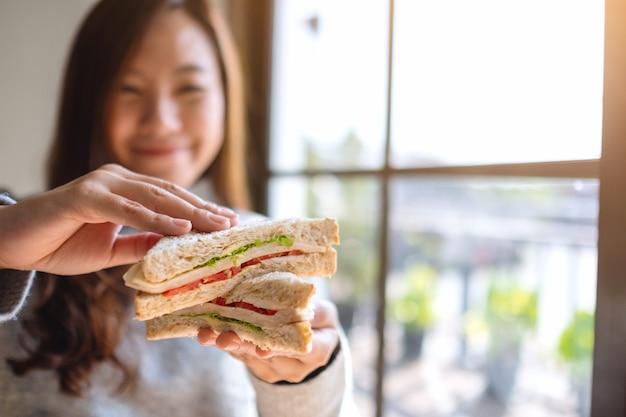 Imagem aproximada de uma mulher asiática segurando e comendo um sanduíche de trigo integral