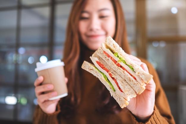 Imagem aproximada de uma mulher asiática segurando um sanduíche de trigo integral e uma xícara de café