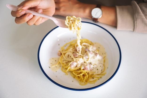 Imagem aproximada de uma mulher comendo espaguete carbonara