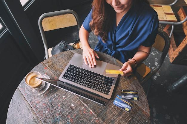 Imagem aproximada de uma mulher de negócios segurando um cartão de crédito enquanto usa um laptop