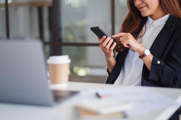 Imagem aproximada de uma mulher de negócios usando um telefone celular no escritório