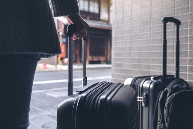 Imagem aproximada de uma mulher segurando e arrastando uma bagagem preta para viajar ao ar livre