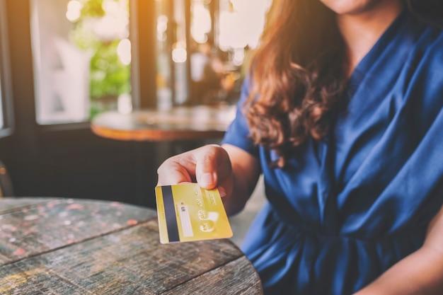 Imagem aproximada de uma mulher segurando e dando um cartão de crédito a alguém