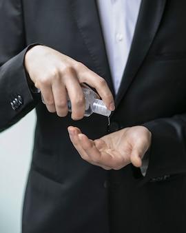 Imagem aproximada de uma pessoa usando um desinfetante para as mãos